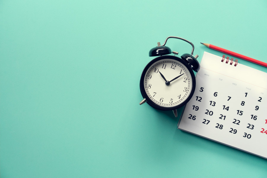 A calendar and clock on a mint background for a blog post about how long it takes to straighten teeth